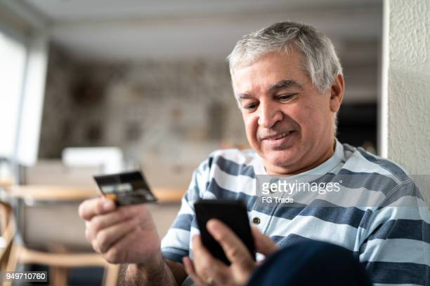 senior purchasing some itens on the internet - brazilian men stock photos and pictures