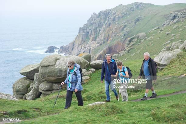 Senior ramblers hiking along rocky coastline, UK.