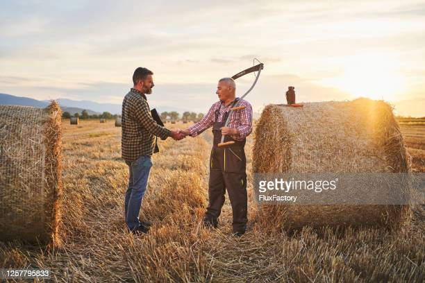 senior rancher made a deal with a mid adult entrepreneur about a hay buy - handshake stock pictures, royalty-free photos & images
