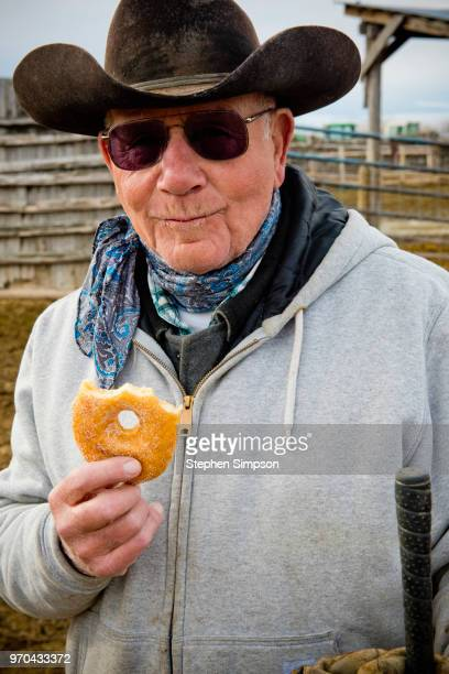 senior rancher takes donut break on montana ranch - montana western usa stock pictures, royalty-free photos & images