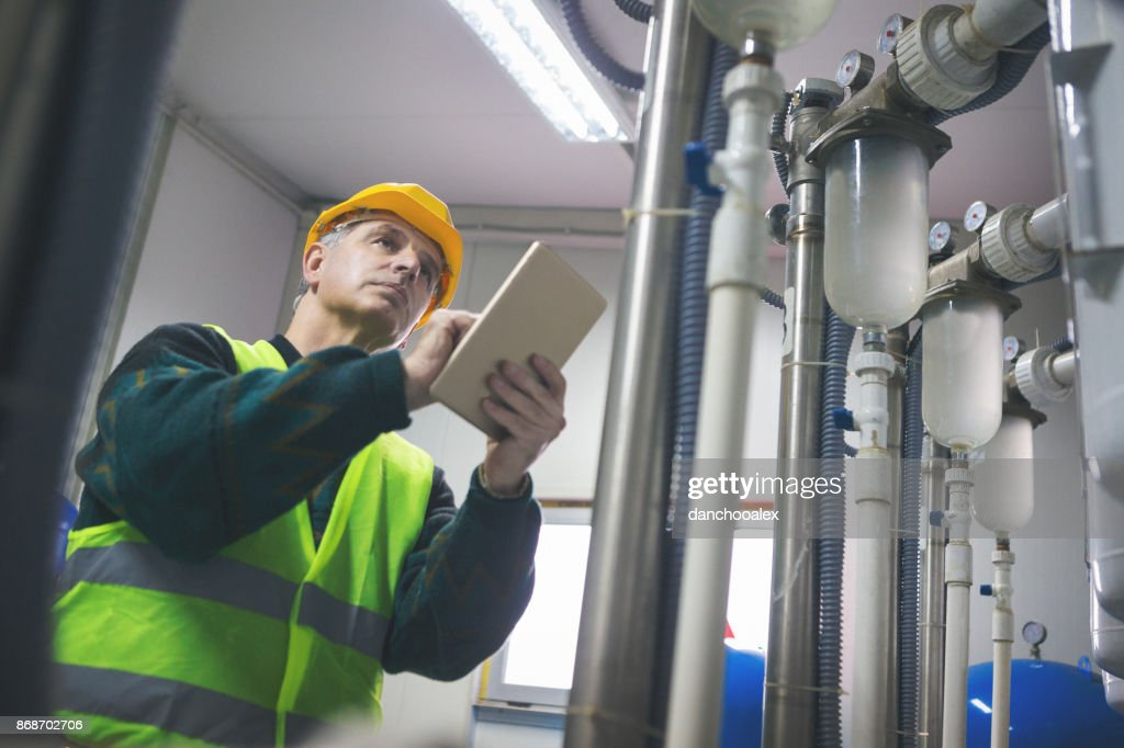 Senior repairman in boiler room checking pipes : Stock Photo