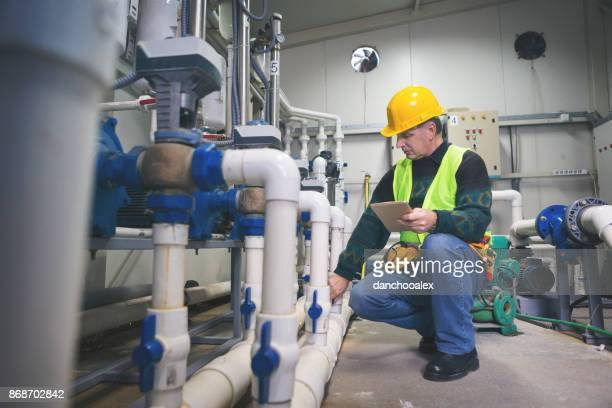 Senior repairman in boiler room checking pipes