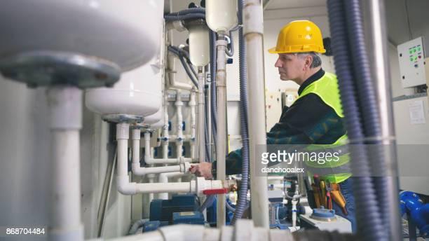 Senior repairman in boiler room checking pipes