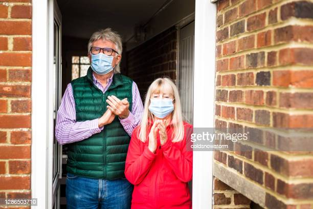 senior retired couple clapping hands at home during covid-19 pandemic - clapping hands stock pictures, royalty-free photos & images
