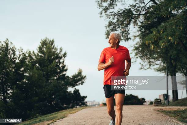 senior retired man runs and performs exercise - jogging stock pictures, royalty-free photos & images