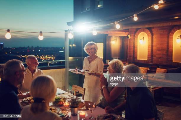 senior rooftop dinner party - evening meal imagens e fotografias de stock