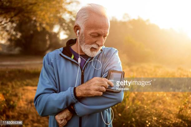 senior runner in nature with smart phone changing music - arm band stock pictures, royalty-free photos & images