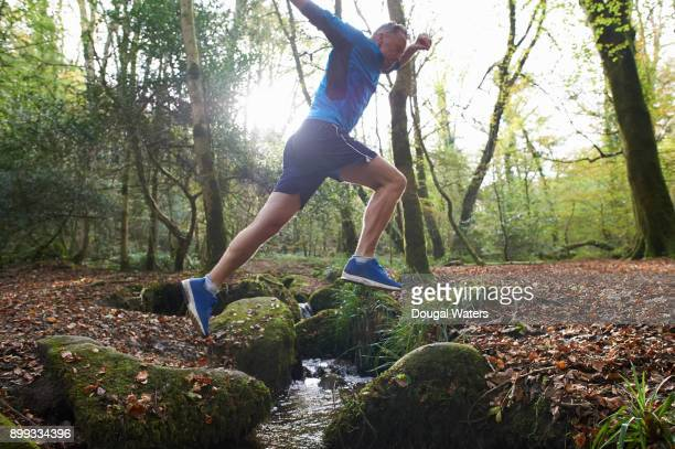 senior runner jumping over woodland stream. - blue shoe stock pictures, royalty-free photos & images