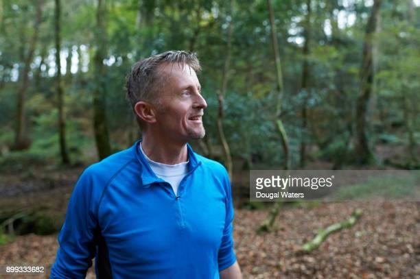 Senior runner outdoors in woodland.