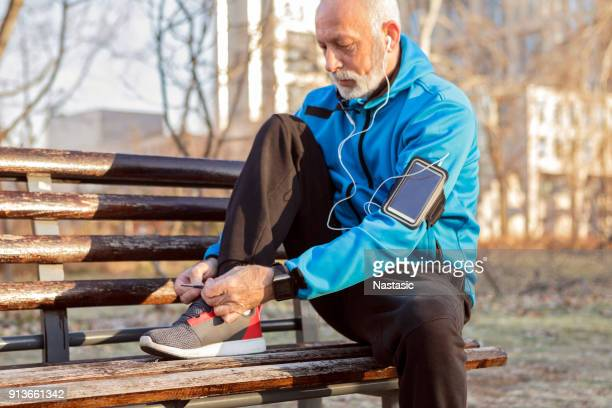 senior runner tying sneakers - tying stock pictures, royalty-free photos & images