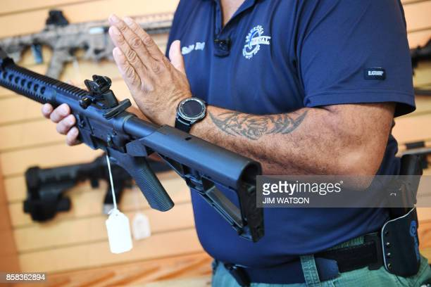 Senior Sales Staff Mark Warner shows a bump stock installed on an AR15 rifle at Blue Ridge Arsenal in Chantilly Virgina on October 6 2017 / AFP PHOTO...