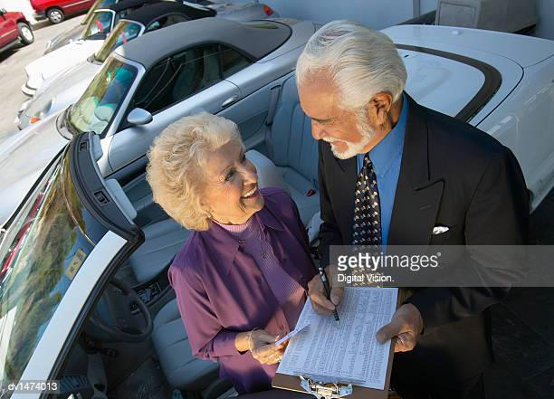 Senior Salesman and Female Customer Stand Next to a New Convertible in a Car Showroom, Signing a Document on a Clipboard