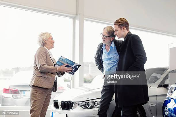 Senior saleswoman explaining brochure to son and father in car dealership shop