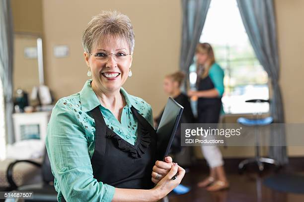 Senior salon owner or hairstylist smiling in beauty shop