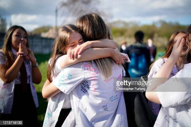 Senior schoolchildren hug and mark their 'leavers' day early as they head home and schools are closed due to the ongoing coronavirus pandemic on...