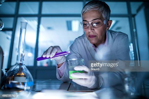 Senior scientist mixing chemical substances during her scientific experiment.
