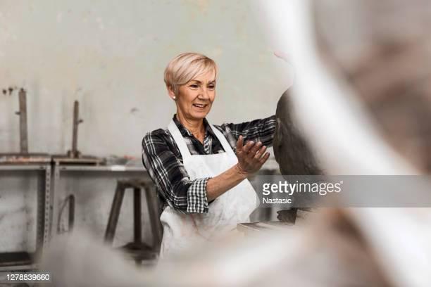 senior bildhauer arbeitet an tonbüste im studio - 55 59 jahre stock-fotos und bilder