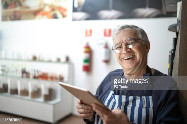 vendedor sênior que usa uma tabuleta digital em uma loja dos produtos naturais - utilizar o tablet - fotografias e filmes do acervo