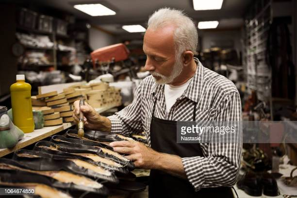 senior shoemaker gluing shoe - leather boot stock pictures, royalty-free photos & images