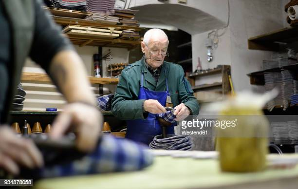 senior shoemaker working on slippers in workshop - working seniors stock pictures, royalty-free photos & images