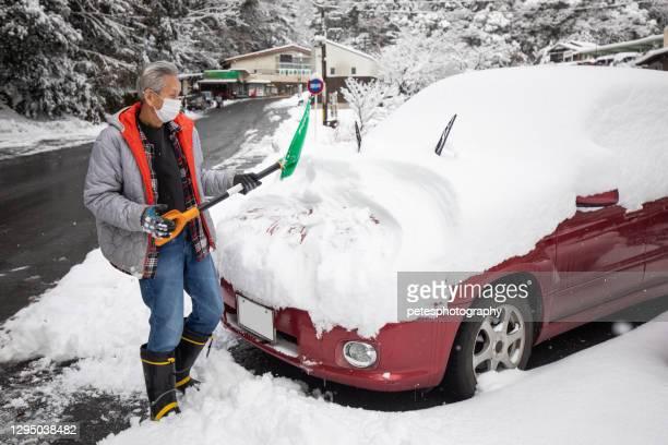 een hogere die sneeuw van zijn auto in de winter schept - diepe sneeuw stockfoto's en -beelden