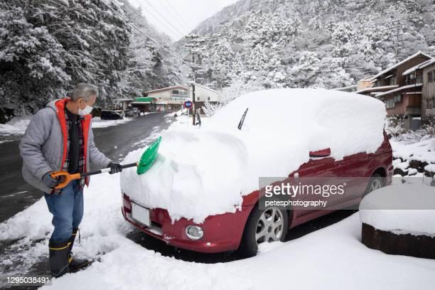 en senior skotta snö från sin bil på vintern - snötäckt bildbanksfoton och bilder
