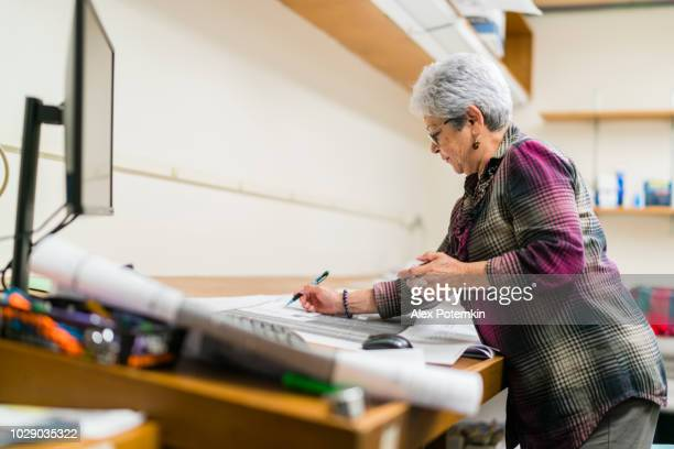 Senior silver-haired woman, engeneer, checking the project using mechanical counter