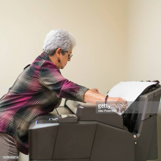 Senior silver-haired woman, engeneer, using the commercial wide format printer