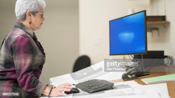 Senior silver-haired woman, engeneer, working with architectural project