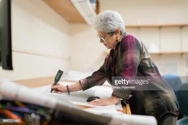 Senior silver-haired woman, engineer, using curvimeter when she working with architectural project