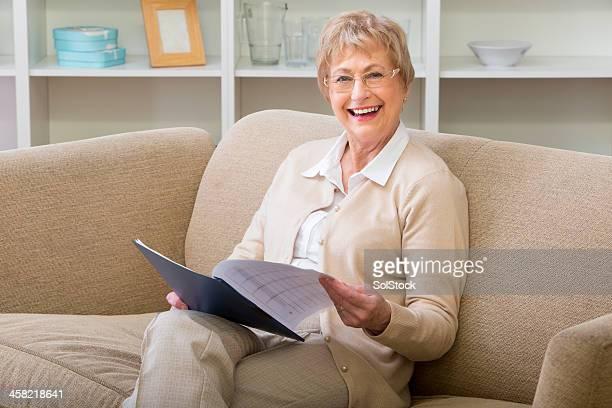 Senior assis avec la lecture d'un Document