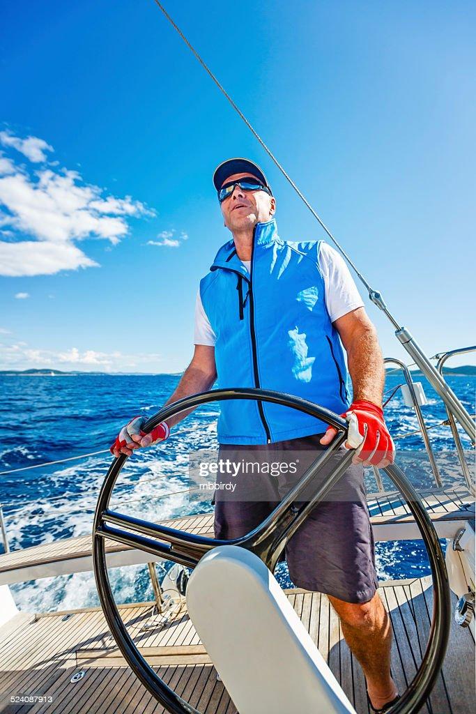 Senior skipper sailing with sailboat : Stock Photo