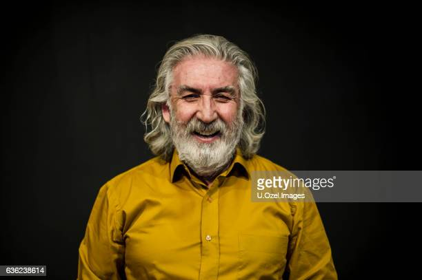 senior smiling man portrait front of a black wall - white hair stock pictures, royalty-free photos & images