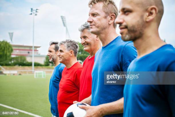 senior soccer players standing in a row before the match - club football stock pictures, royalty-free photos & images