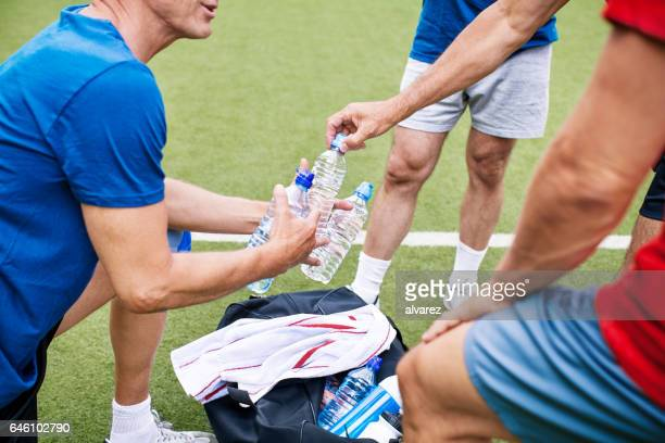 Senior soccer players taking break and drinking water