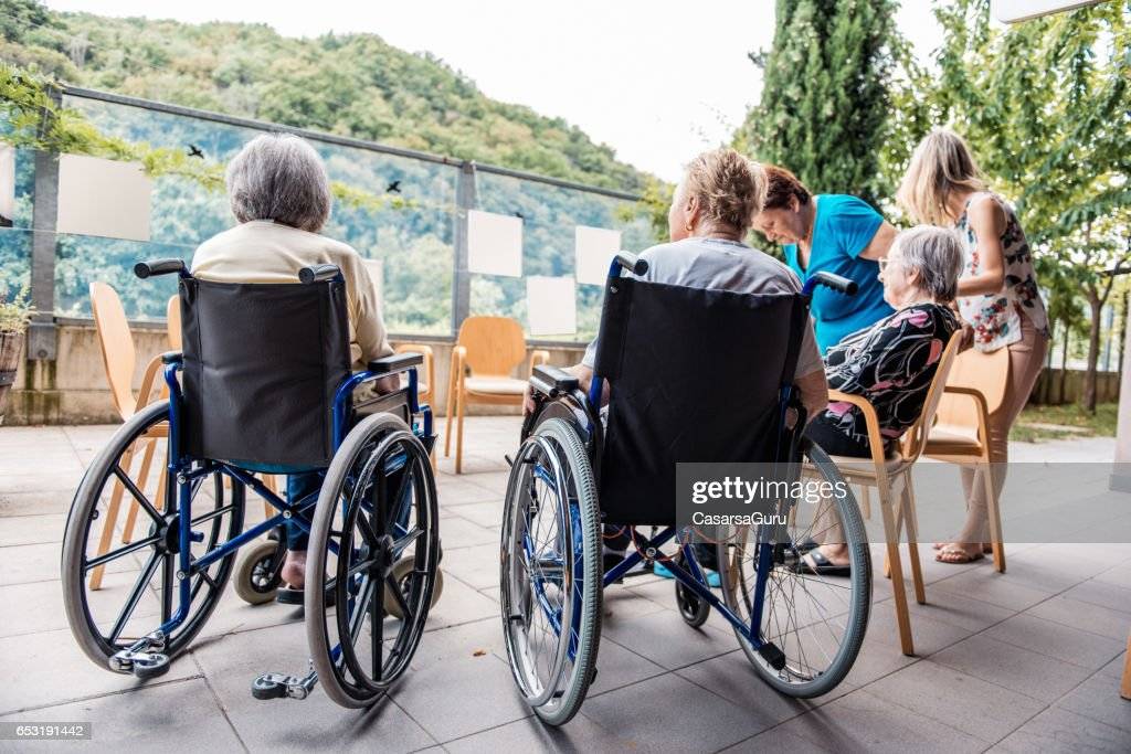 Senior Socializing Outside In The Retirement Home : Stock Photo
