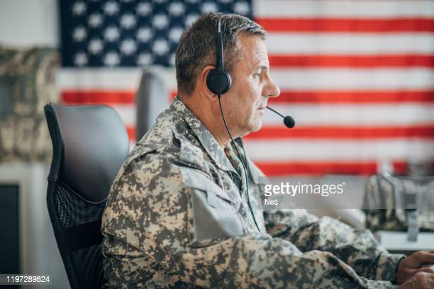 senior soldier using headphones and microphone - armed forces day stock pictures, royalty-free photos & images