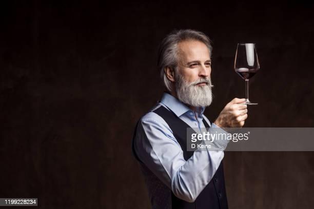 赤ワインを味わうシニアソムリエ - ワインセラー ストックフォトと画像