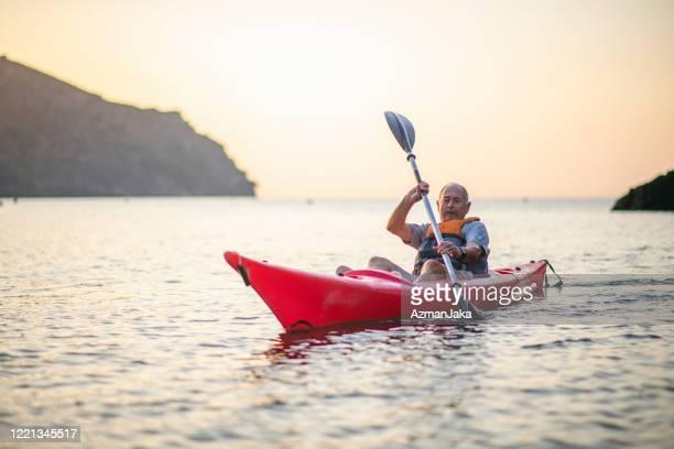 senior spanish kayaker exercising in mediterranean at dawn - sea kayaking stock pictures, royalty-free photos & images