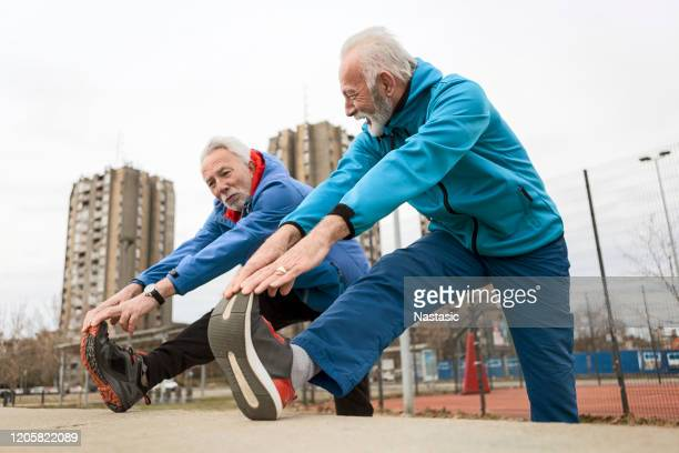 senior sportsman stretching legs - human leg stock pictures, royalty-free photos & images