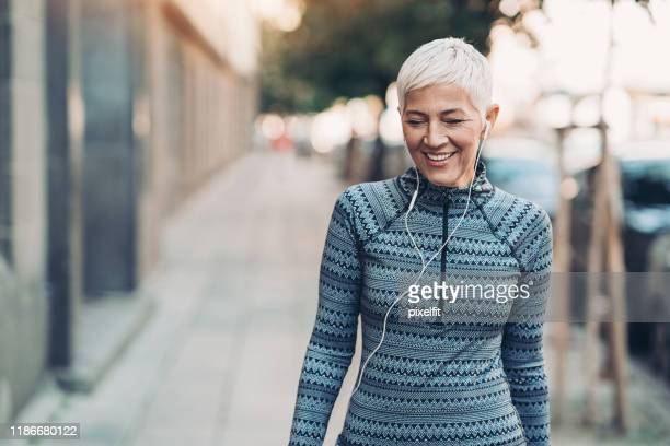 senior sportswoman walking on the street - active lifestyle stock pictures, royalty-free photos & images