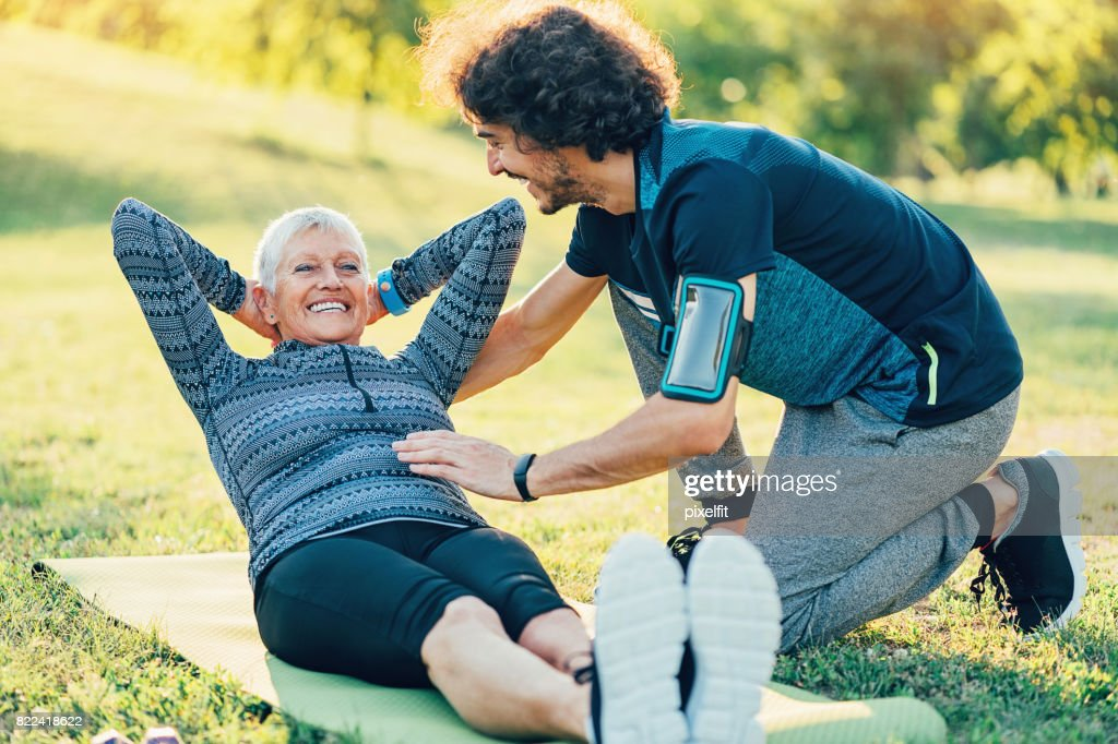 Senior sportswoman with a personal instructor : Stock Photo