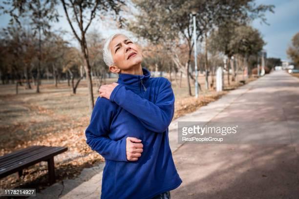 シニアスポーティな女性は、公園で肩の痛みを持っています - 関節 ストックフォトと画像