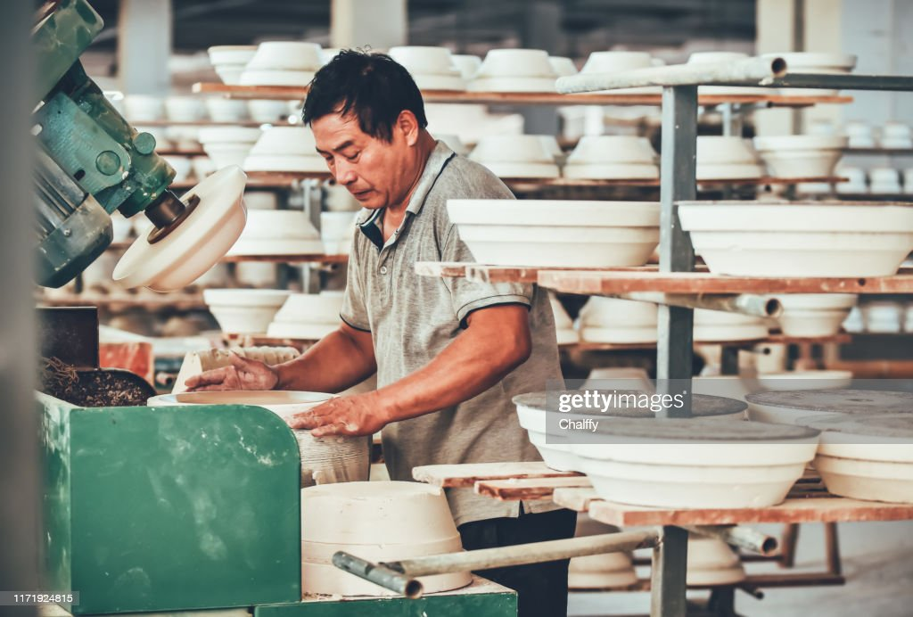A Senior Staff Polishing Porcelain Clay in Factory : Stock Photo