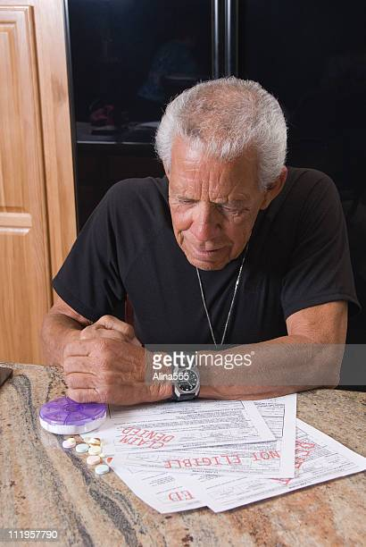 senior staring at his denied medical bills - forbidden stock pictures, royalty-free photos & images