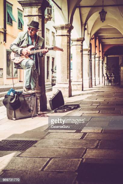 Senior Street Artist Enjoying Playing Electric Guitar in the Street