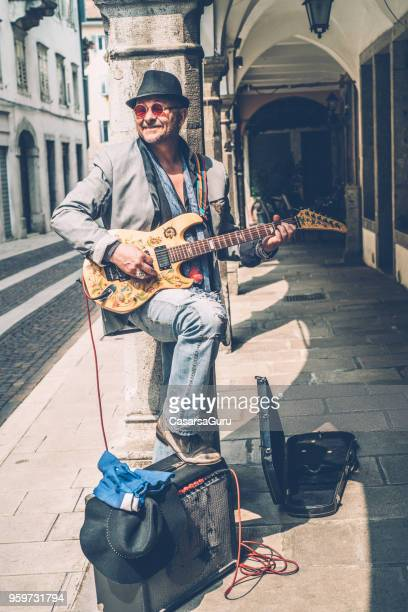 senior street artist enjoying playing electric guitar in the street - street artist stock pictures, royalty-free photos & images