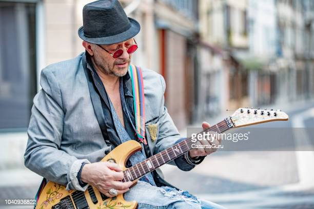 senior street performer playing electric guitar on city street - rocker stock photos and pictures
