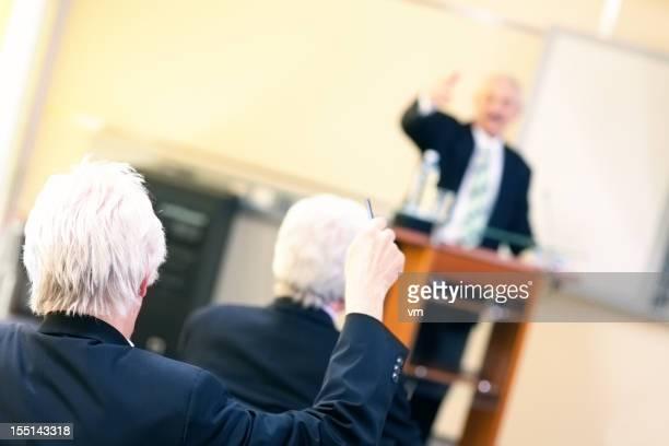 Älterer student Anhebung hand bei business-seminar