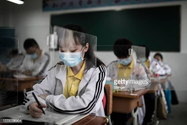 Senior students study in a classroom with transparent boards placed on each desk to separate each other as a precautionary measure against the spead...